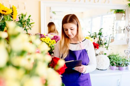 Young owner of flower shop writing in her notebook. Small business