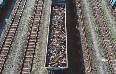 Drone boven zicht op spoorwagon gevuld met schroot. Metaalrecycling