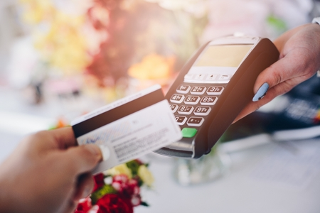 work less: Man paying for flowers with his debit card. Credit card payment