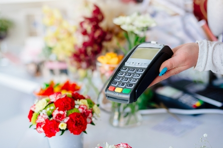 technology transaction: Credit card payment. Florist shop owner holding credit card terminal.