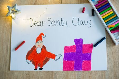 Child pastel drawing of Santa Claus and present. Wish list