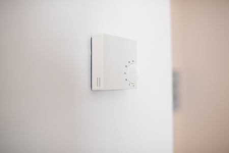 Home heating regulating thermostat on the wall