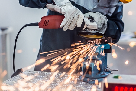Worker cutting metal with angle grinder. Metalwork in factory