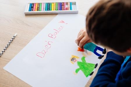 彼のおばあちゃんのためのグリーティングカードを描く幸せなポーランドの子供。ポーランド語おばあちゃんの日!