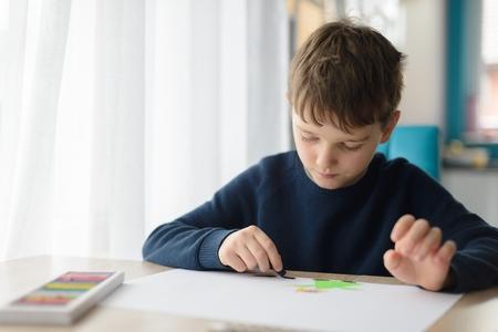 おばあちゃんの日のために彼のおばあちゃんのためのグリーティングカードを描く幸せな8歳の男の子の子供。おばあちゃんの日おめでとう!