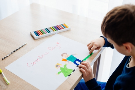 Happy 8 years boy child drawing a greeting card for his grandma for Grandma Day. Happy Grandmother Day! Stock Photo