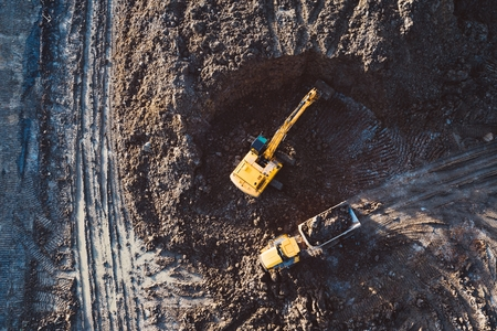 Aerial drone view of excavator loading the tipper truck at the construction site Stock fotó