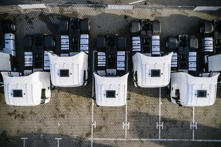 Aerial drone view of parked white trucks. Road transport Stock Photo