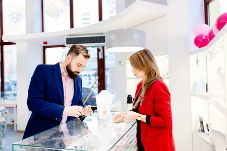 Beauty female seller presents a necklace. Jewelry store. Woman jeweler. Attractive man with a beard choosing a valentines day gift in jewelry store Stockfoto