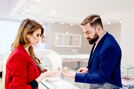 Beauty female seller presents a necklace. Jewelry store. Woman jeweler. Attractive man with a beard choosing a valentine's day gift in jewelry store Zdjęcie Seryjne