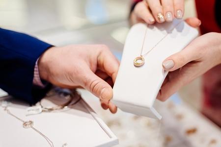 Mężczyzna kupuje naszyjnik w sklepie jubilerskim. Sprzedaż i obsługa klienta w sklepie Zdjęcie Seryjne