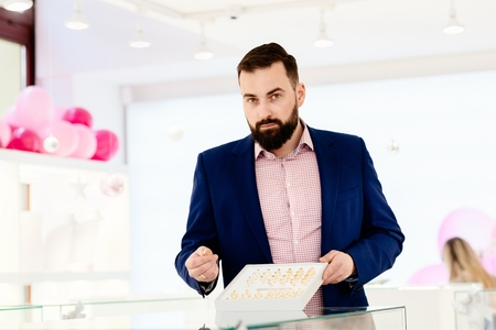 Attractive man with a beard showing a collection of wedding rings. Buying wedding ring. Customer service in jewelry store. Banque d'images