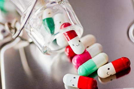Capsule pills with smile on reflective surface. Stockfoto