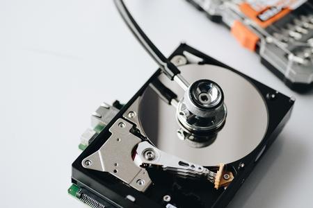 Hard disk drive health. Medical stethoscope on opened hard disk