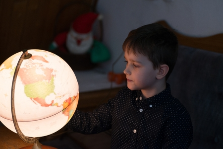 Little fascinated boy is planning another trip on an illuminated globe 版權商用圖片