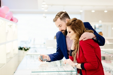 Young couple buying ring in jewelry store. Valentines Day gift