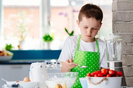 Happy child boy adding sugar to bowl and preparing a cake. Child helping in kitchen