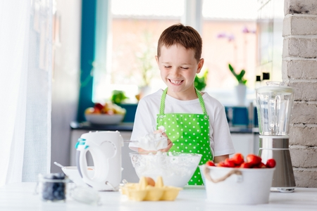 Happy child boy trying sweet dough and preparing a cake. Child helping in kitchen