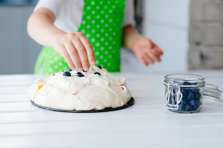 Happy child decorating meringue with blueberries . Child helping in kitchen Stock Photo