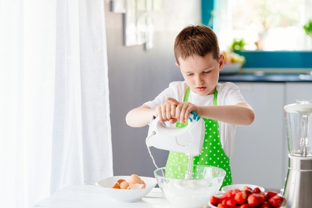 Happy child boy mixing dough in glass bowl and preparing a cake. Child helping in kitchen