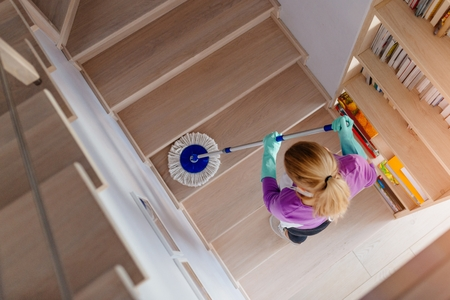 Young woman in white apron cleaning stairs. Cleaning service. Maid cleaning at home Фото со стока