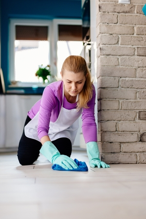 Young woman in white apron washing floor on her knees. Maid cleaning at home