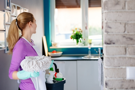 Young woman in rubber gloves holding mop and bucket with detergens. Maid cleaning at home Stock Photo
