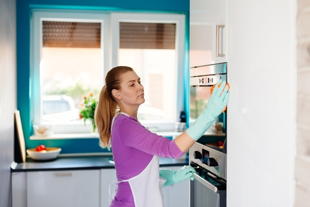 Young woman in rubber gloves cleaning oven. Maid cleaning at home Banque d'images