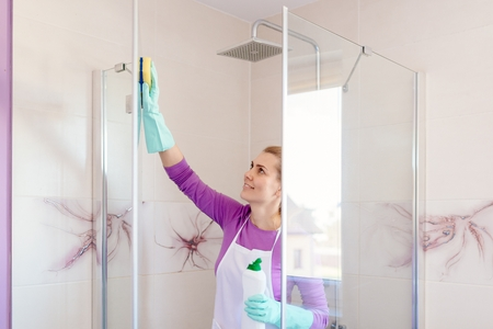 Young beautiful woman in white apron cleaning shower cabin. Cleaning service. Maid cleaning at home Stock fotó