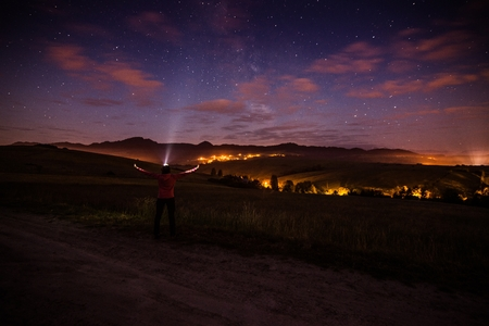 Young happy woman at starry night in mountains. Pointing flashlight light to the sky. Freedom and relax concept