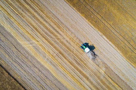 Aerial drone view of tractor plowing field after harvesting. Farm works