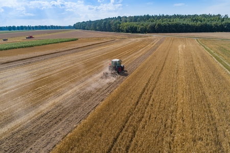Tractor plowing field after harvesting. Farm works