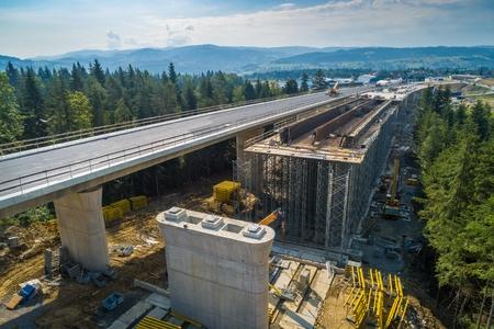 Luftdrohnenansicht auf der im Bau befindlichen Autobahnstraße. Bau des Viadukts auf der Nationalstraße Nr. 7 in Polen Standard-Bild