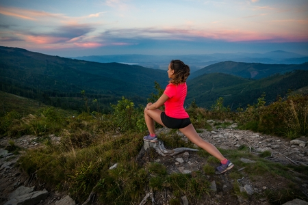 Young woman stretching after trail cross country running in mountains. Polish silesian Beskid, Szczyrk, Poland