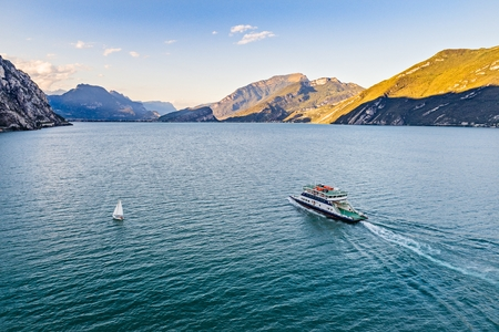 Aerial drone view on car ferry on calm waters of Lake Garda in Italy, Limone sul Garda