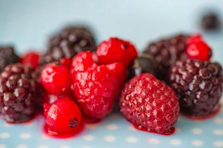 Melting fruits on the plate. Melting frozen raspberry and blackberry Standard-Bild