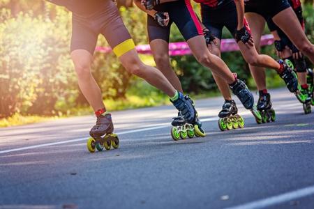 Pattinatori in linea che corrono nel parco su strada asfaltata