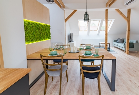 Set wooden table in modern dining room. Modern bright flat apartment in the attic