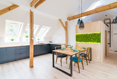 Wooden set table and modern kitchen in the attic with black kitchen cabinets