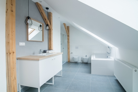 Bright modern bathroom with grey walls, mirror and bathtub. Modern bright flat apartment in the attic