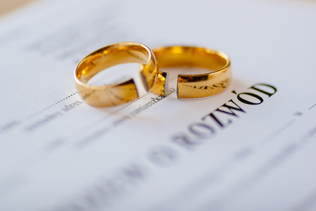 Divorce decree in Polish language and two broken wedding rings. Divorce and separation concept