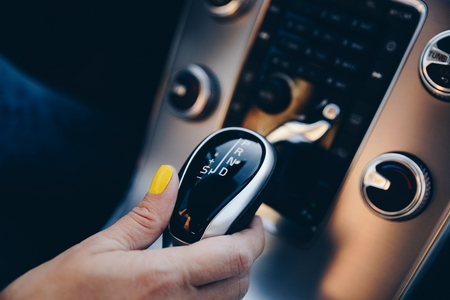 Woman changing modes in automatic gearbox. Woman driving a car 스톡 콘텐츠