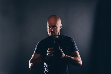 Man paparazzi photographer portrait in studio. Photographer with dslr camera