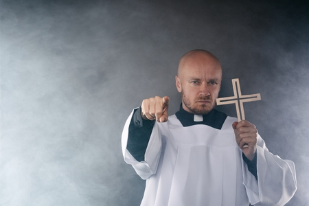 Catholic priest exorcist in white surplice and black shirt with cleric collar praying with crucifix Stock Photo