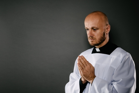 Catholic priest in white surplice meditates and prays