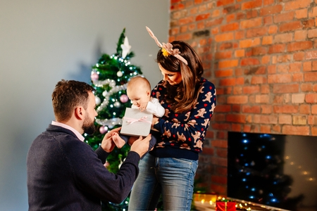 Young parents with their baby at Christmas. Family at Christmas. Merry Christmas!