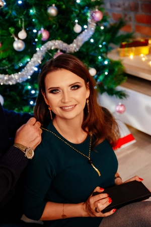 Man helps his wife to wear jewelry necklace at Christmas. Puts necklace on her neck. Christmas surprise.