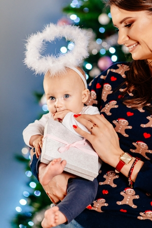 Alone mother with her baby at Christmas. Baby first Christmas Stock Photo