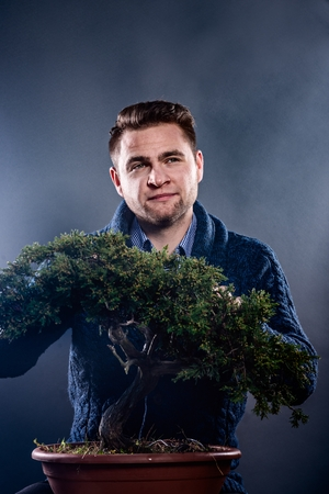 Studio shot of young man pruning japanese bonsai tree. Hobby and passion concept