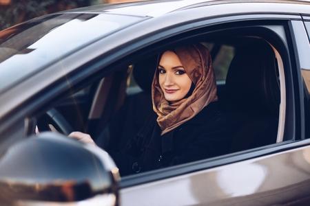 Giovane donna araba in hijab alla guida di un'auto